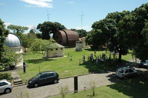 imagem aérea do gramado do campus com pessoas e o pavilhão restaurado ao fundo