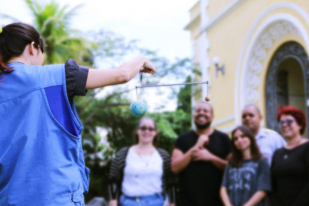 mediadora dando explicações a grupo de visitantes